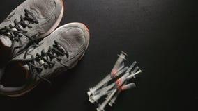 掺杂:很多注射器在附近落运动鞋-慢动作,顶视图 股票视频