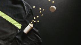 掺杂:有药片的容器在体育T恤杉-慢动作,顶视图落 股票视频