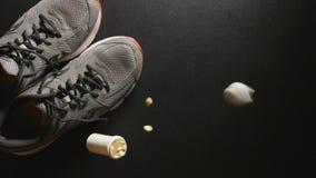 掺杂:有药片的容器在附近落运动鞋-慢动作,顶视图 股票录像