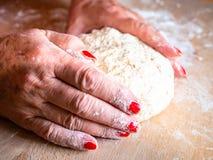揉和按摩家制面包面团的端庄的妇女手 图库摄影