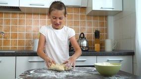 揉在黑暗的桌上的年轻快乐的女孩面团在厨房里 股票录像