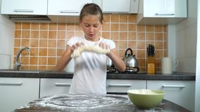 揉在黑暗的桌上的年轻快乐的女孩面团在厨房里 股票视频