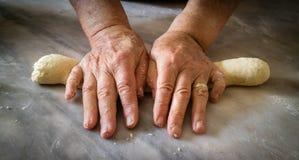 揉面团的年长妇女的手做新鲜的生物意大利面团 库存照片