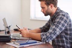 描出使用他的手机的观点的白人在书桌 免版税库存图片