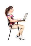 描出研究膝上型计算机的女小学生的射击 库存图片