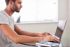 描出研究他的计算机的年轻白种人人的图象 免版税库存照片