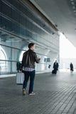 描出走与手提箱和咖啡杯的一个年轻人的画象在机场终端附近 免版税库存照片