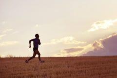 描出跑在夏天日落的乡下训练的年轻人剪影 免版税库存照片