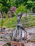 描述一个球的一个美丽的喷泉一个女孩在一个绿色公园 步行的地方 免版税库存照片