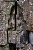 描述在Ta Phrom寺庙废墟,吴哥窟柬埔寨墙壁上的浅浮雕古老故事  库存照片