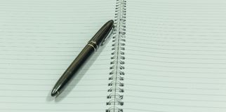 描述有一黑葡萄酒penImage的图象空白的螺纹笔记本描述有一个黑葡萄酒笔地方的空白的螺纹笔记本 库存图片
