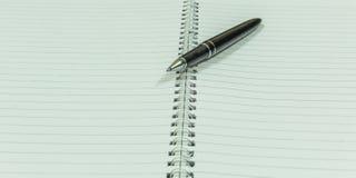 描述有一黑葡萄酒penImage的图象空白的螺纹笔记本描述有一个黑葡萄酒笔地方的空白的螺纹笔记本 免版税库存照片