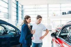 描述汽车的销售主任对顾客 免版税图库摄影