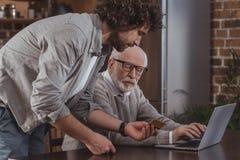 描述资深父亲的成人儿子侧视图怎么对在网上购物与信用卡 免版税库存图片