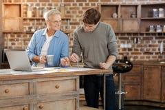 提他的年轻同事关于图画的老人建议 免版税库存照片