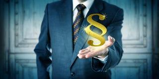提供一个金黄部分标志的男性律师 免版税库存照片