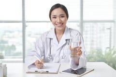 提供一杯水的微笑的女性医生在她的办公室 库存图片