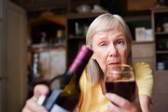 提供一杯酒的醉酒的妇女 免版税库存照片