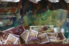 提供为菩萨的金钱在西藏古老修道院里 免版税库存照片