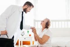 提供关心为老人 在家拜访年长患者的医生 免版税库存图片