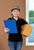 提供包裹的交付妇女拿着剪贴板 免版税图库摄影