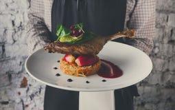 提供可口餐馆盘的侍者 免版税库存图片