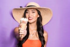 提供圆锥形的冰淇淋杯和看的海滩服装的快乐的亚裔妇女 免版税库存照片