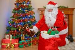 提供圣诞节礼物的圣诞老人 库存照片