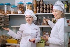 提供在地方骗局的白色长袍的微笑的女职工甜点 图库摄影