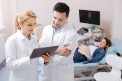 提供在诊所的高兴的医疗同事专业任命 免版税库存照片