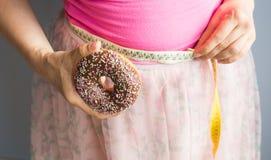 提供多福饼手中和检查的妇女他的与测量的磁带的体脂肪 免版税库存照片