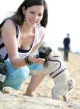 提供她的妇女年轻人的狗 免版税库存图片