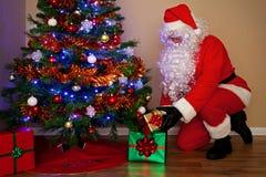 提供存在的圣诞老人在结构树下。 免版税库存照片