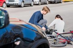 提供急救的有用的年轻人一名受伤的妇女在bicke事故以后 免版税图库摄影