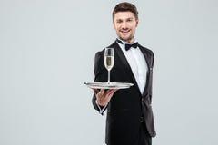 提供您杯香槟的无尾礼服的快乐的男管家 图库摄影
