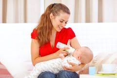 提供愉快的母亲坐的沙发的婴孩 免版税库存图片