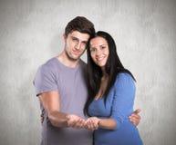 提供手的年轻夫妇的综合图象 库存图片
