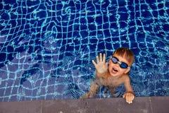 提供援助照相机的游泳场的滑稽的男孩 免版税图库摄影