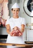 提供新鲜的肉的确信的女性屠户 库存照片