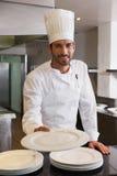 提供板材的愉快的主厨微笑对照相机 免版税图库摄影