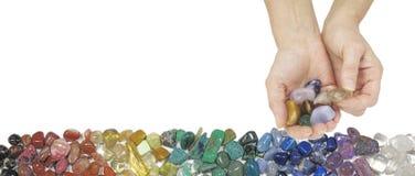 提供柠檬色翻滚的石头的水晶治疗师 免版税库存照片