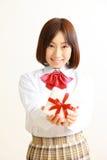 提供礼物的女性高中学生 图库摄影
