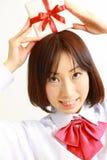 提供礼物的女性高中学生 免版税图库摄影