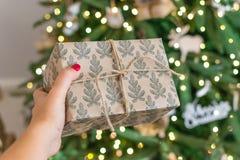 提供礼物的手对圣诞树 新年是2019年 在土气样式的顶楼树,礼物栓与绳索 免版税库存图片