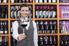 提供红葡萄酒玻璃的侍酒者反对架子 免版税库存图片