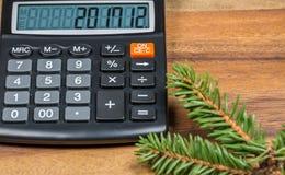 提供经费给有新年数字的计算器在显示和云杉的树枝 关闭 免版税库存照片