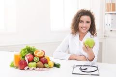 提供绿色苹果的营养师妇女在照相机 免版税库存照片