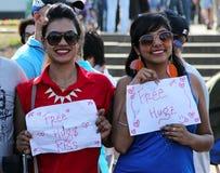 提供自由拥抱的两个微笑的美丽的女孩在Cosplay节日 库存照片