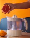 提供葡萄柚的一半的女孩在紧压它前与一台电柑橘榨汁器 免版税库存照片
