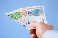 提供援助欧洲钞票的商人的手 免版税库存图片
